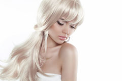 Beautiful blond girl with long hair isolated on white background. Fashion model posing at studio Stock Photos
