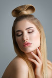 Beautiful blond girl with long hair. Beautiful young woman with long straight blond hair and fancy hairdo on top of head. Eyes closed. Studio shot on grey Royalty Free Stock Photography