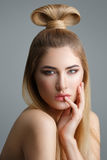 Beautiful blond girl with long hair. Beautiful young woman with long straight blond hair and fancy hairdo on top of head. Eyes closed. Studio shot on grey Stock Photography
