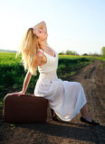 Beautiful blond girl in long white dress, sitting on suitcase Royalty Free Stock Image