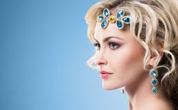 Beautiful blond girl with luxury golden jewelry. Woman wearing golden jewelery with crystals. stock photography