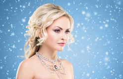 Beautiful blond girl with luxury golden necklace over blue winter background. Christmas concept. royalty free stock photo