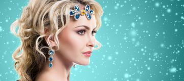 Beautiful blond girl with luxury golden necklace over cyan winter background. Christmas concept. royalty free stock photo