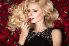 Beautiful blond girl lying on background of roses. Curls, red lipstick, evening dress. beauty face. Stock Photo