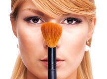 Beautiful blond girl with make-up brush Stock Photo