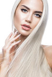 Beautiful blond girl in move with a perfectly smooth hair, and classic make-up. Beauty face. royalty free stock photo