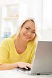 Beautiful blond girl with a notebook at home Stock Image