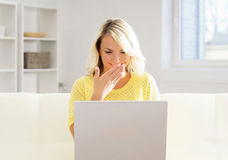 Beautiful blond girl with a notebook pc at home Royalty Free Stock Images
