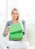 Beautiful blond girl opening a gift. Green box Stock Images