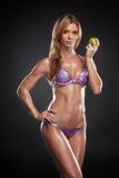 Beautiful blond girl with perfect figure holding apple. Royalty Free Stock Photos