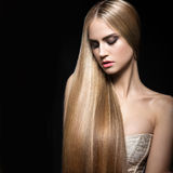 Beautiful blond girl with a perfectly smooth hair and classic make-up. Beauty face. Royalty Free Stock Image