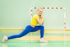 Beautiful blond girl performing the forward lunge Stock Photo