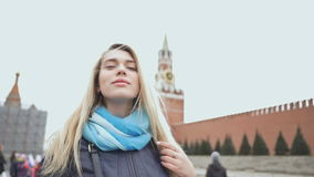 Beautiful blond girl posing against a red square in Moscow. Russia. stock footage