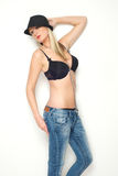 Beautiful blond girl posing in bra and black hat Stock Photography