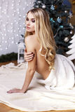 Beautiful blond girl posing beside a Christmas tree Stock Photo