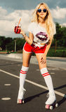 Beautiful blond girl posing on a vintage roller in T-shirt and red shorts in sunglasses and enjoy the summer drink. Outdoor. Beautiful blond sexy girl posing on Stock Photo