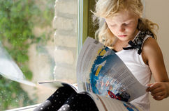 Beautiful blond girl reading book Royalty Free Stock Images