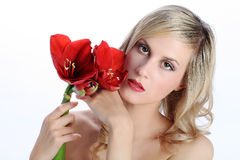 Beautiful blond girl with red amaryllis flower on a white Royalty Free Stock Photo
