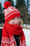 Beautiful blond girl  in red cap and scarf.Traditional   Christmas decorative knitted pattern in Scandinavian style Royalty Free Stock Photography
