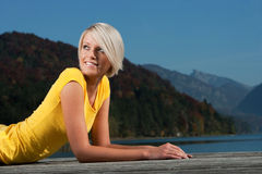 Beautiful blond girl relaxing on a wooden jetty Royalty Free Stock Photography