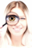 Beautiful blond girl's eye in a loupe Royalty Free Stock Images