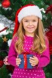 Beautiful blond girl in Santa hat smiling on camera. royalty free stock image
