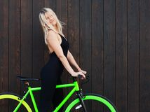 Beautiful blond girl in sexy outfits posing with a fixed bicycle on the background of their old wooden boards on the. Street. the wind blows her hair. Outdoor Stock Image