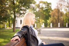 Beautiful blond girl sitting on a bench Royalty Free Stock Images