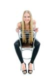 Beautiful   blond girl sitting on chair Stock Photos