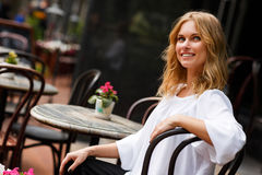 Beautiful blond girl sitting in street cafe on summer day Stock Images