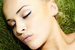 Beautiful blond girl sleeping on green grass. beauty woman Stock Photography