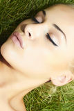 Beautiful blond girl sleeping on green grass. beauty woman Stock Image