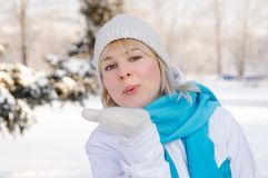 Beautiful blond girl in sportswear sends an air kiss. Directly to the camera. winter forest Royalty Free Stock Images