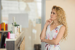 Beautiful blond girl thinks what to buy in cafe Stock Images