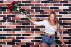 Beautiful blond girl throwing roses up and laughing Royalty Free Stock Images