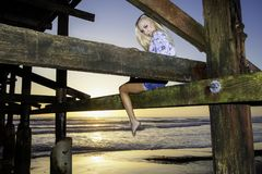 Blond girl under a pier Royalty Free Stock Photo