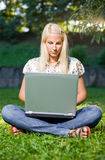 Beautiful blond girl using laptop in the park.. Stock Photos
