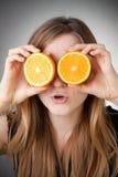 Beautiful blond girl using orange as glasses Royalty Free Stock Images