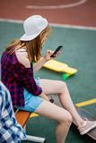 A beautiful blond girl wearing checkered shirt, cap and denim shorts is sitting on the sports field with a phone in her royalty free stock images