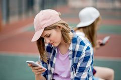 A beautiful blond girl wearing checkered shirt and a cap is sitting on the sports field with a phone in her hand. Sport royalty free stock photography