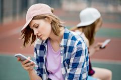A beautiful blond girl wearing checkered shirt and a cap is sitting on the sports field with a phone in her hand. Sport royalty free stock image