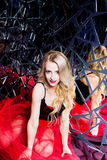 Beautiful blond girl wearing a corset and red skirt in a mirror Royalty Free Stock Image