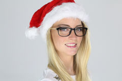Beautiful blond girl wearing glasses and a santa hat Royalty Free Stock Image