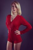 Beautiful blond girl wearing a red bodysuit Stock Photos