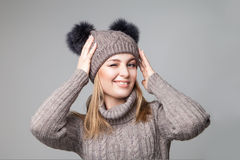 Beautiful blond girl wears winter pullover and hat Royalty Free Stock Photography