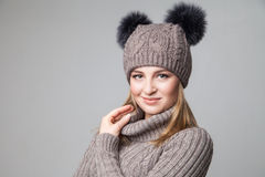 Beautiful blond girl wears winter pullover and hat Stock Photo