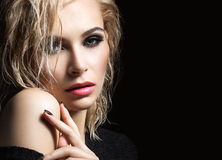 Beautiful blond girl with wet hair, dark makeup and pale lips. Beauty face. Picture taken in the studio on a black background stock images