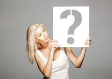 Blond girl holding a question mark sign. Beautiful blond girl in white dress holding a question mark sign Royalty Free Stock Photo