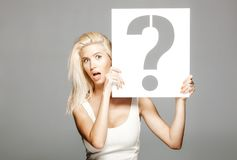 Blond girl holding a question mark sign. Beautiful blond girl in white dress holding a question mark sign Stock Images