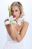 Beautiful blond girl with white lily flower on a white Royalty Free Stock Photo